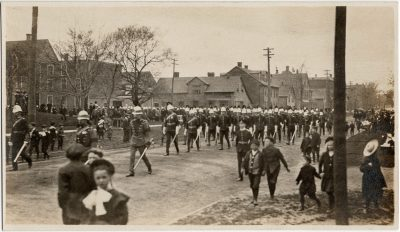 """, Parade – Possibly Boer War uniforms. From Harry Holman: These two pics are taken from the east     side of Prince Street. One is from a spot just south of the corner with Kent Street looking     south. The other is just south of the corner with Grafton St. Looking north.   The """"grasssy     knoll"""" in the military parade photo is the NE corner of St. Paul's church grounds.  The church     tower and the distinctive shape of the eve of the Sunday School building can be faintly seen on     the photo facing south.  None of the buildings on the view facing north have survived. The corner     building was replaced by Zion Presbyterian church about 1911. The three story brick building on     the north view was a grocery story on the corner of Prince and Kent.  I attach a copy of an     insurance atlas image ca. 1903 showing this block.   The houses are the same in both photos.  It     is interesting that the views show the parade both coming and going (if they are the same parade,     which is questionable).  The military parade route is east on Grafton and then south on Prince.     The fraternal order parade is heading north on Prince Street. They are both at the same time of     the year so it could be the same event. Unlikely to be the opening or closing of the legislature     as the fraternal bodies did not participate.  Lots of other parades however during Jubilee     celebrations, Boer war events and coronations. See also 3178 (3177), PEI Postcards"""